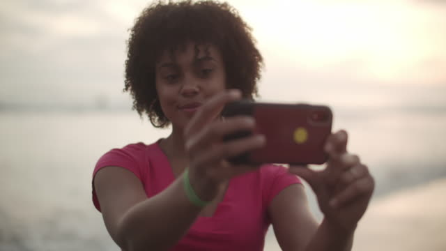 ms young woman taking a selfie at the beach - teenage girls stock videos & royalty-free footage