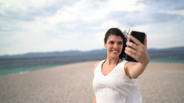 young woman taking a selfie at the beach - one young woman only stock videos & royalty-free footage