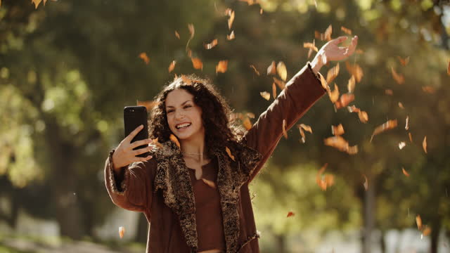 stockvideo's en b-roll-footage met sm young woman taking a selfie in the fall leaves - zelfportret fotograferen