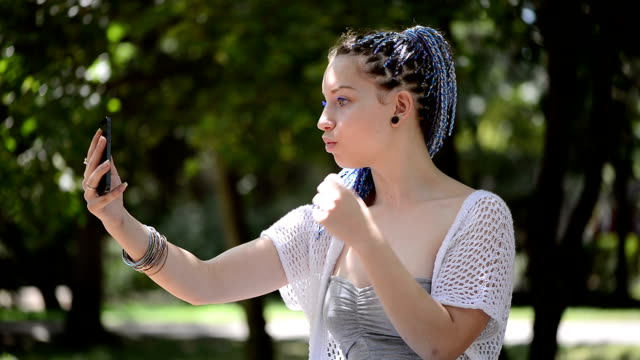 Young woman taking a selfie in the park