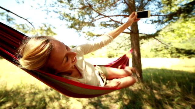 junge frau, die ein selfie auf hängematte - hängematte stock-videos und b-roll-filmmaterial