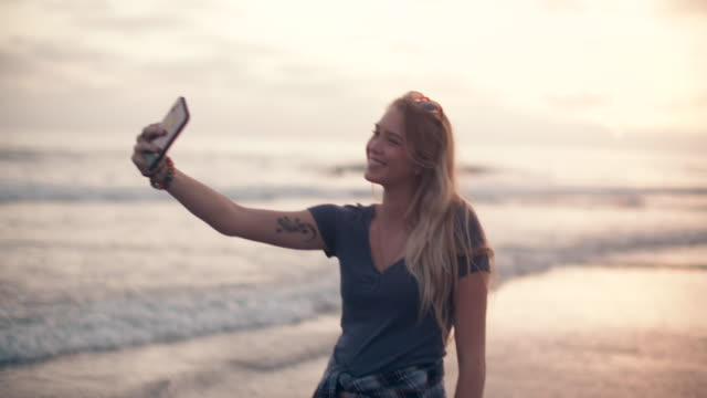 ms young woman taking a selfie on the beach - selfie video stock e b–roll