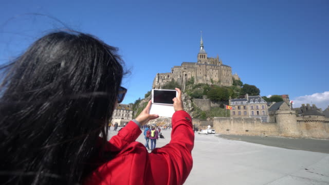 cneutrv1093 young woman taking a selfie photo at mont saint michel - normandy stock videos and b-roll footage