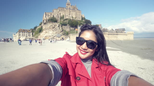 giovane donna scattare un selfie foto un mont saint michel - selfie video stock e b–roll