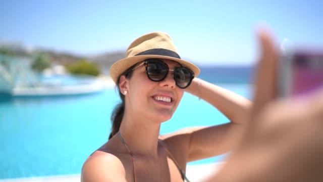 スイミングプールの前でスマートフォンでセルフィーを撮る若い女性 - 自画像点の映像素材/bロール