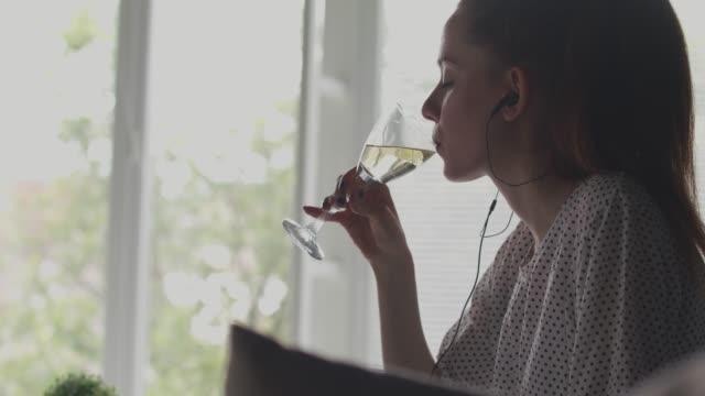 junge frau nimmt einen schluck weißwein während eines videoanrufs mit einem freund - weinglas stock-videos und b-roll-filmmaterial