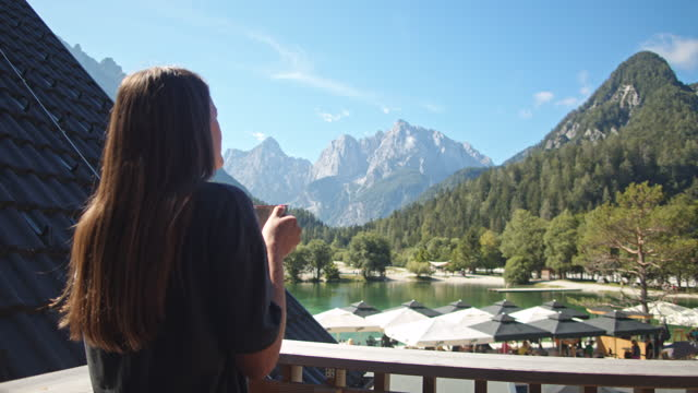slow motion young woman taking coffee on the balcony to enjoy the view - balcony stock videos & royalty-free footage