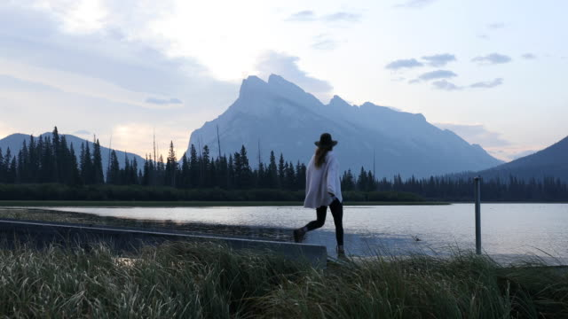 vídeos de stock, filmes e b-roll de a young woman taking in sunrise from a dock in banff national park. - píer