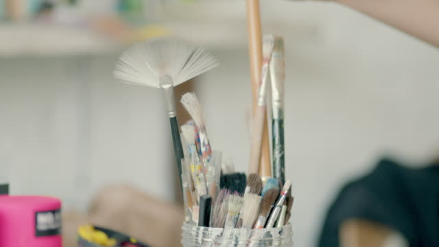 young woman taking paint brushes - 刷毛点の映像素材/bロール