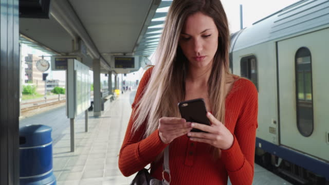 young woman taking phone out of purse to send text while at train station - borsetta video stock e b–roll