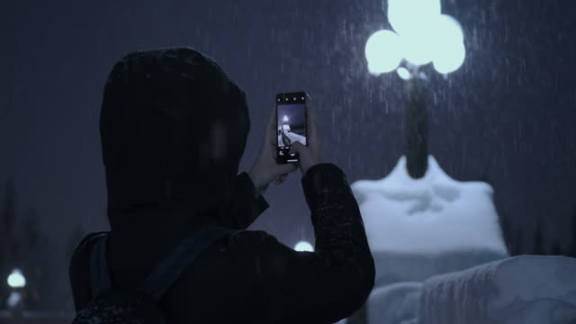 young woman taking photo in snowing at night - photographing stock videos & royalty-free footage
