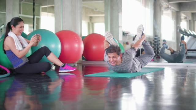 young woman taking photo of a man exercising at gym - bow pose stock videos & royalty-free footage