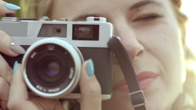 young woman taking photo with retro camera - photographing stock videos and b-roll footage