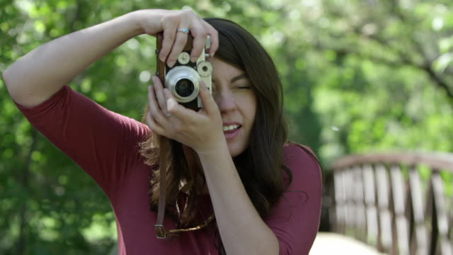 young woman taking photo with vintage film camera - photographer stock videos & royalty-free footage