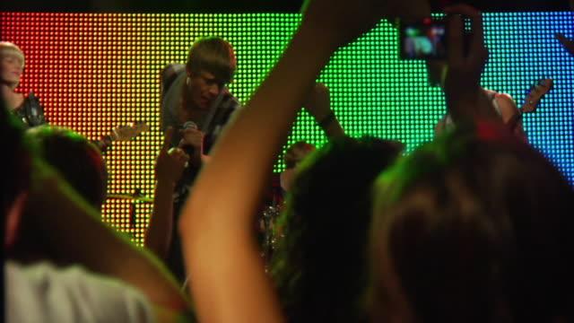 ms r/f slo mo young woman taking photograph at rock concert / london, uk - 30 34 ��r bildbanksvideor och videomaterial från bakom kulisserna