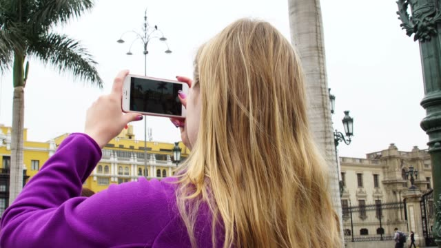 young woman taking photos at plaza de armas in lima, peru - lima stock videos & royalty-free footage