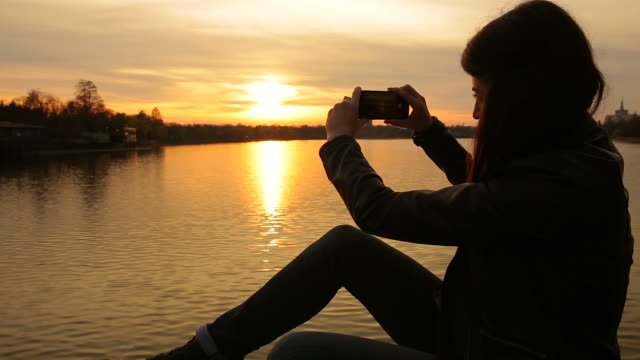 Young woman taking photos at sunset.