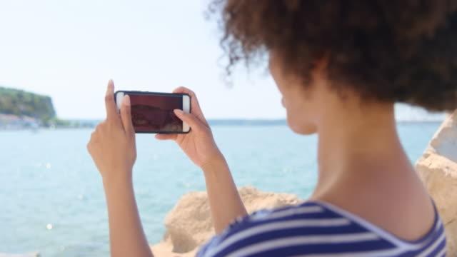 vídeos de stock, filmes e b-roll de jovem mulher tirando fotos da bela cidade costeira em um dia ensolarado - cabelo encaracolado
