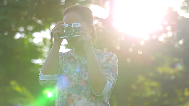young woman taking photos with old film camera in garden