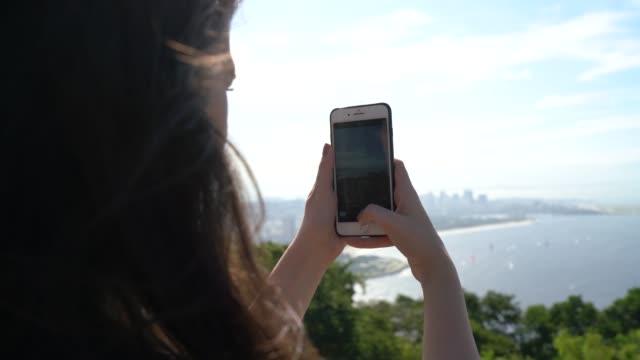 vídeos de stock, filmes e b-roll de mulher nova que toma o retrato das montanhas em rio de janeiro - discovery