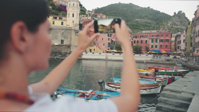 Young woman taking pictures in Cinque Terre - Vernazza village