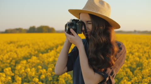 slo mo ms young woman taking pictures in field of rape - photographer stock videos & royalty-free footage