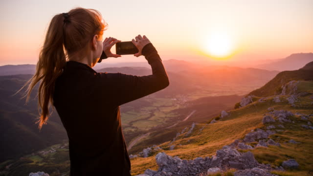 Young woman taking pictures of sunset with her smartphone