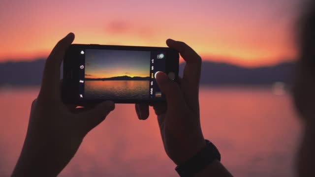 young woman taking pictures of the beautiful view with smartphone - photograph stock videos & royalty-free footage