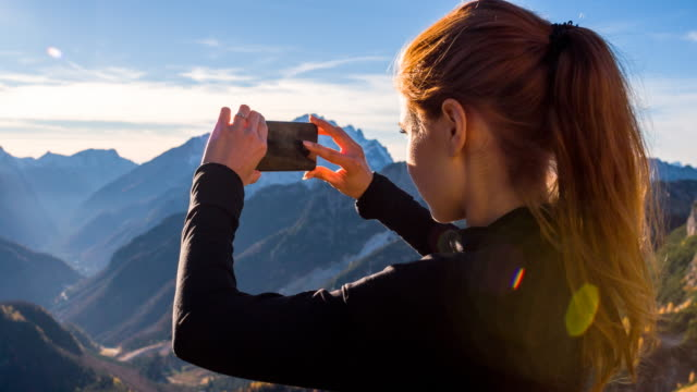 young woman taking pictures of the beautiful view with smartphone - photographing stock videos & royalty-free footage