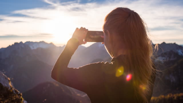 young woman taking pictures of the beautiful view with smartphone - mountain peak stock videos and b-roll footage