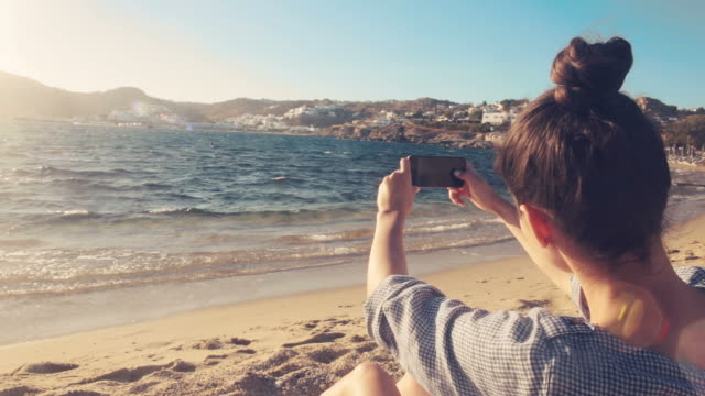 young woman taking pictures with a smart phone. - mykonos stock videos and b-roll footage