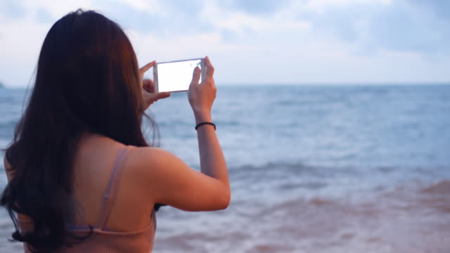 Young woman taking pictures with smartphone