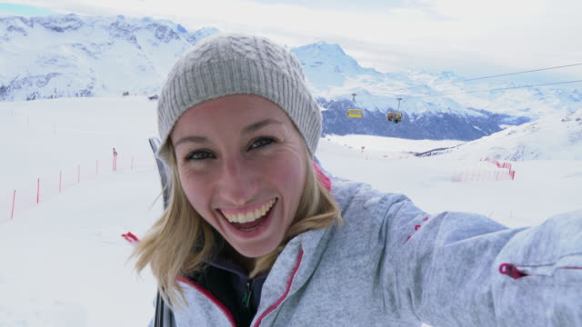 Young woman taking selfie on ski slopes
