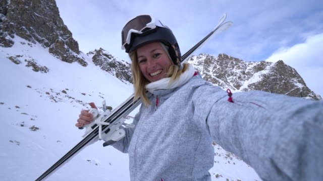 young woman taking selfie on ski slopes - stazione sciistica video stock e b–roll