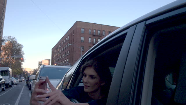 Young woman taking selfie out of car window, daytime