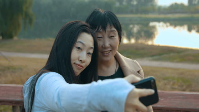 Young woman taking selfie with her mother