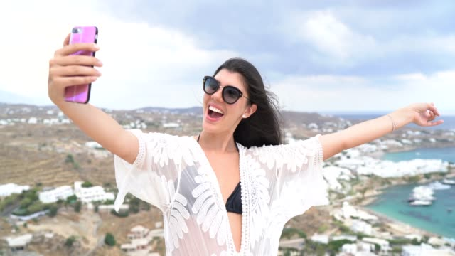young woman taking selfie with smartphone in the top of a hill, mykonos city and bay on the background - careless stock videos & royalty-free footage