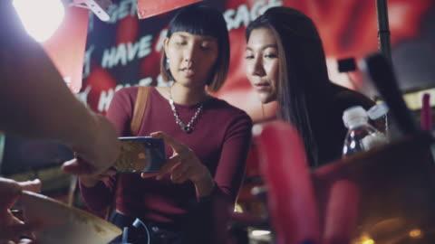 ung kvinna tar selfie med street food omelett i khao san road. - bangkok bildbanksvideor och videomaterial från bakom kulisserna