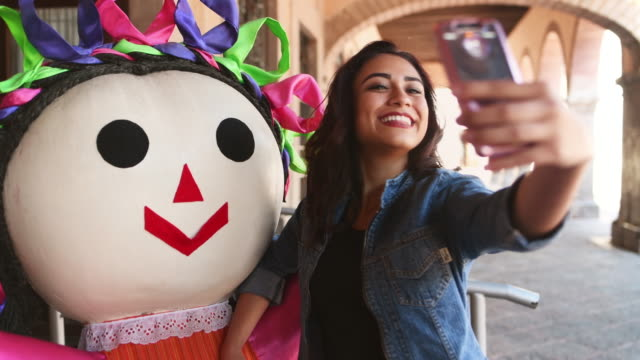young woman taking selfie with traditional mexican doll - america latina video stock e b–roll