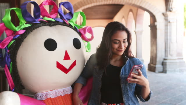 Young woman taking selfie with traditional Mexican Doll