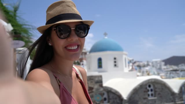 young woman taking selfies during vacations in greek island - santorini stock videos & royalty-free footage