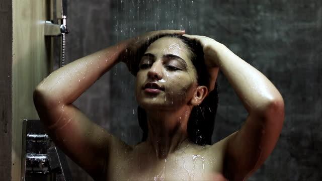 young woman taking shower in bathroom, delhi, india - 浴室点の映像素材/bロール