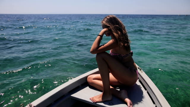 young woman taking the sun in a boat. relaxation and sunbathing on deck - uv protection stock videos and b-roll footage