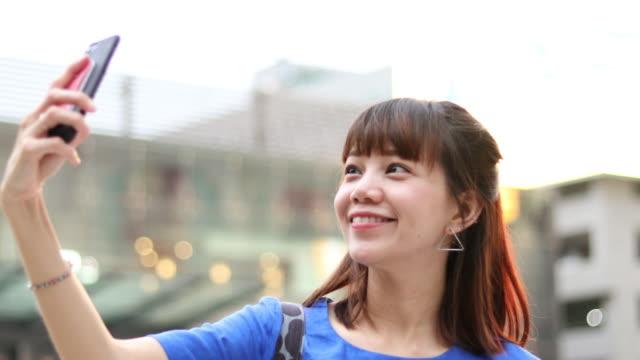 junge frau im gespräch einer selfies an sehenswürdigkeit in bangkok thailand - only young women stock-videos und b-roll-filmmaterial