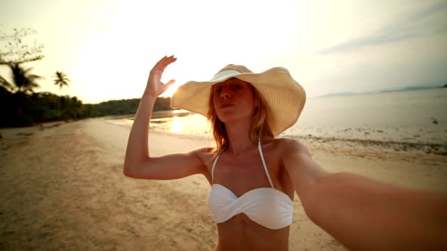 Young woman talking a selfie on tropical beach at sunset