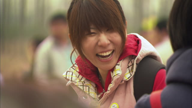 CU Young woman talking and laughing with friends during tree planting ceremony / Beijing, China
