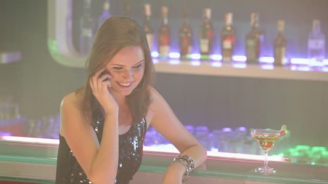 Young woman talking in a mobile phone at bar counter