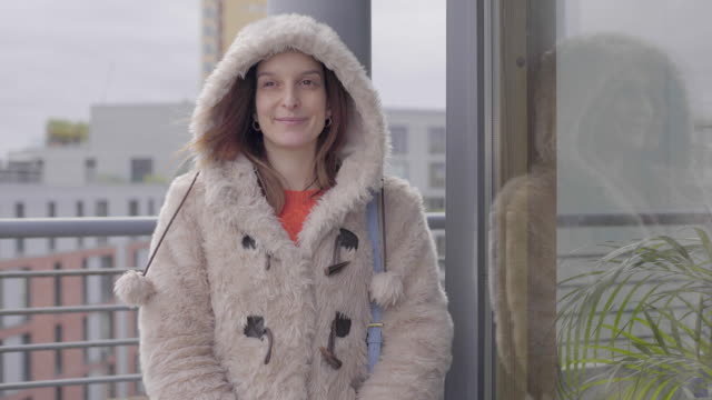 a young woman talking on a balcony in winter. - winter coat stock videos & royalty-free footage