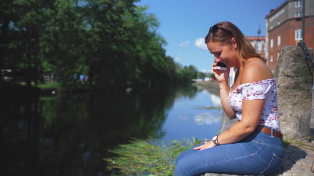 Young Woman Talking on a Mobile Phone by Canal