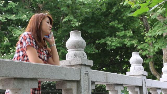 young woman talking on a smartphone at a landing - korta ärmar bildbanksvideor och videomaterial från bakom kulisserna